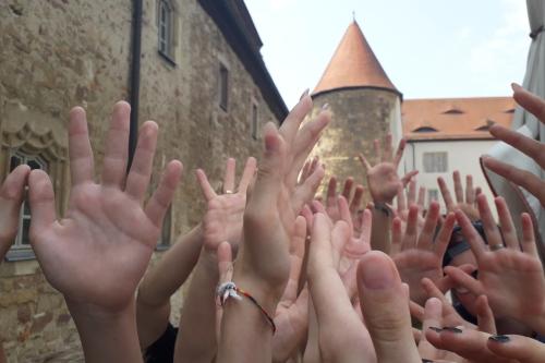 Kinder und Jugendliche halten Hände nach oben